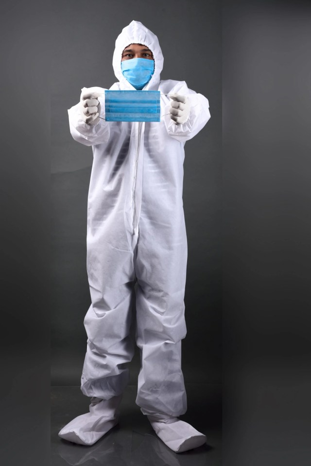 Man in PPE holding mask