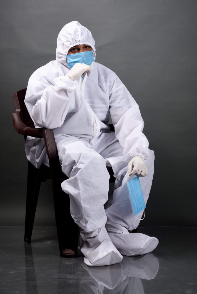 Man on chair in PPE kit