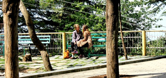 Two girls sitting on bench near railing