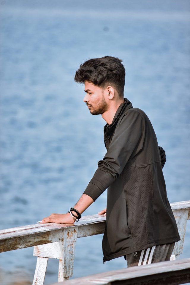 A boy standing at a riverfront