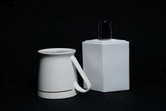 A tea cup and perfume bottle