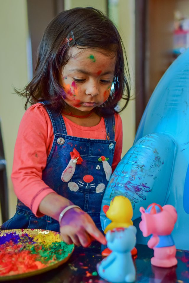 A little girl playing with holi colors
