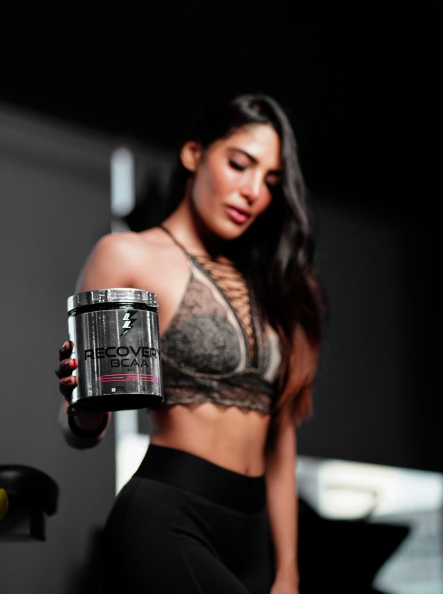 Female fitness model showing her supplement box