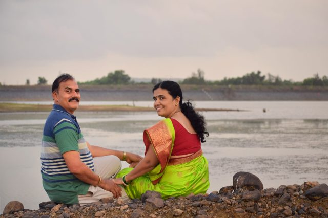 Indian happy couple sitting near a lake