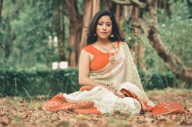 Female model posing in the forest while wearing saree