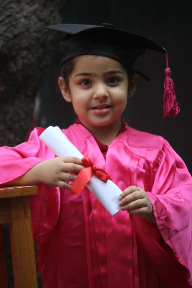 A little girl in graduation day getup
