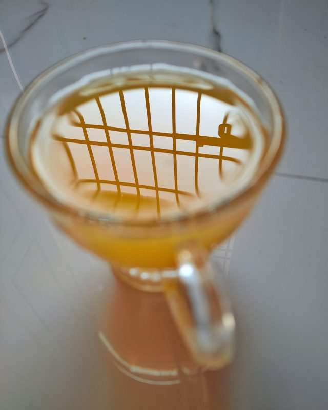 Window reflection in a juice glass
