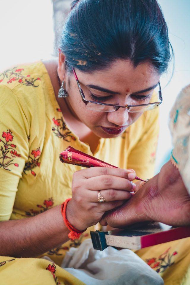 Woman applying Mehendi on bride's leg