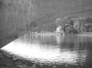Schwarzweißbild. Blick vom Rive-Ufer aus durch die Giebichensteinbrücke in Halle (Saale), flußaufwärts, auf ein im Trafohäuschen im Villenstil und einen kleinen Aussichtsfelsen.