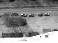 Schwarz-Weißbild. Blick aus dem neunten Stock nach unten: Fußweg, geparkte Autos, Bäume, Straße, Schatten