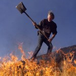 man fighting grass fire blaze with shovel