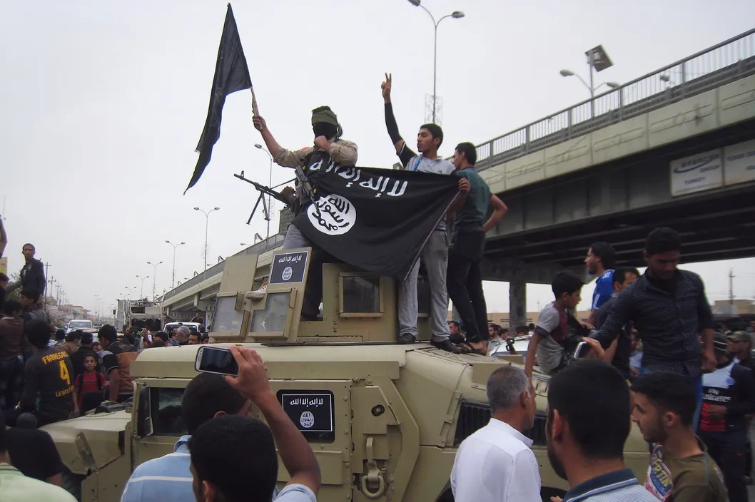 ISIS fighters celebrate on vehicles taken from Iraqi security forces in Fallujahon March 30, 2014.