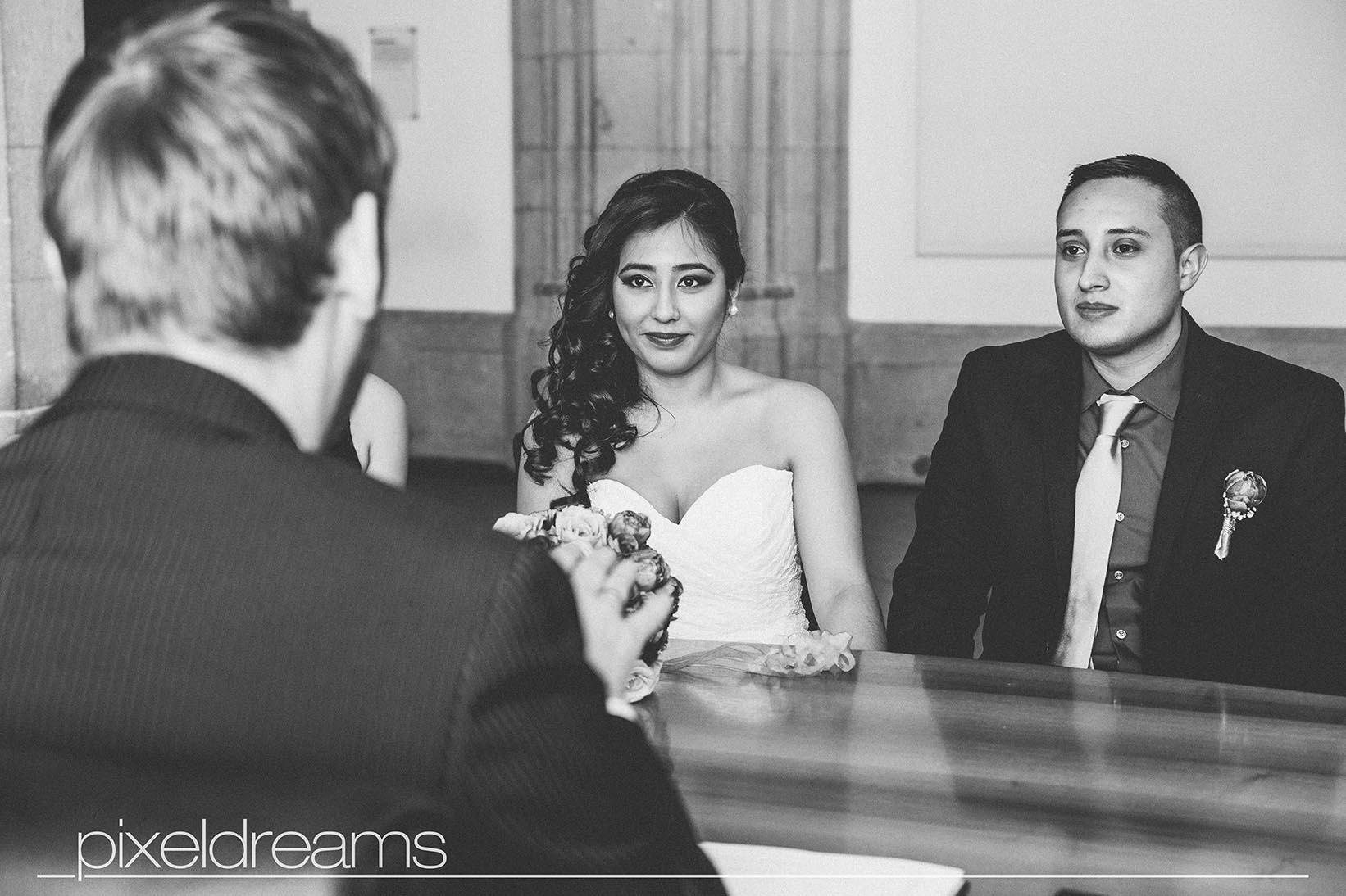 Braut und Bräutigam sitzen vor dem Standesbeamten und lassen sich gleich trauen - die reportage erfolgt durch unseren hochzeitsfotografen von pixeldreams