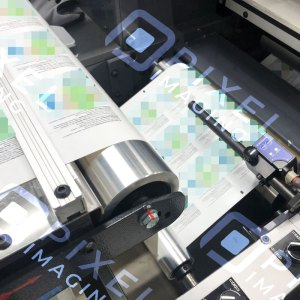 Custom-printed product labels being printed on a label printing machine.