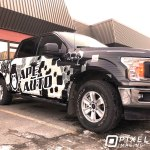 A custom-printed partial vinyl vehicle wrap on the side of a Ford pickup truck.