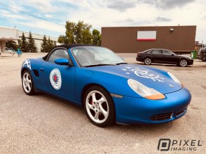 Vinyl car wrap on a blue Porsche car with side decals, hood decals, and fender decals