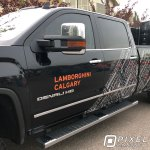 Vinyl lettering and a custom-printed partial vinyl vehicle wrap on a GMC Denali HD pickup truck.
