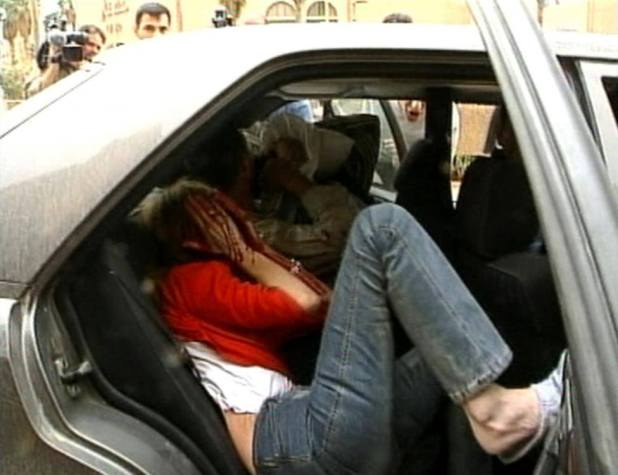 Samia Nakhoul, now Reuters Middle East Editor, is seen in the back of a car after being wounded at the Palestine Hotel in Baghdad, April 8, 2003, in this image taken from video footage. A U.S. tank fired a shell at the hotel from which she was reporting. REUTERS/Pool via Reuters TV
