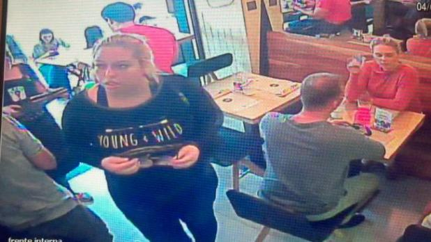 The woman in black whose job it was to distract Brett Costello so his bag could be stolen. via CCTV/DailyMail