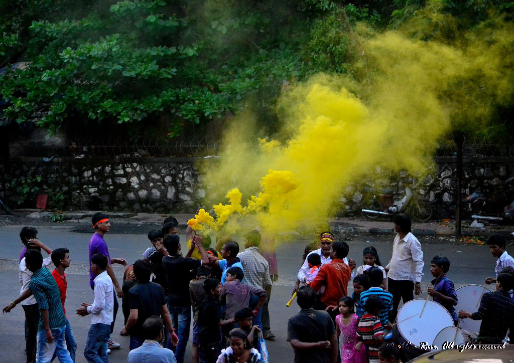 Coloured powder is thrown in the air during a procession
