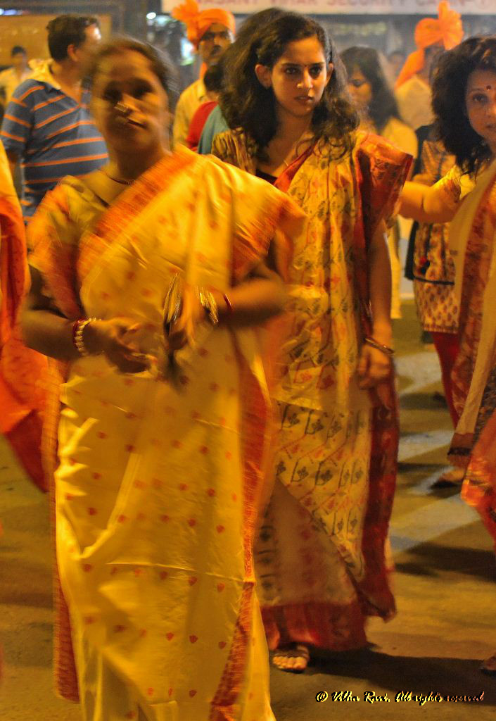 Bengali women walk in a procession during Durga Pooja