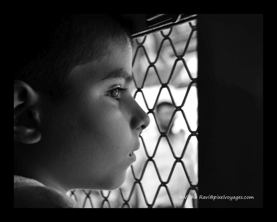 Child in Mumbai suburban train looks out a window
