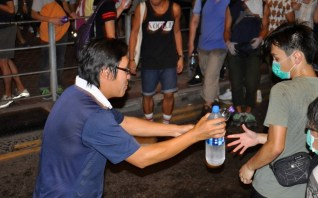 Shortly after the police deploy tear-gas, citizens hand down water down a human supply line-up