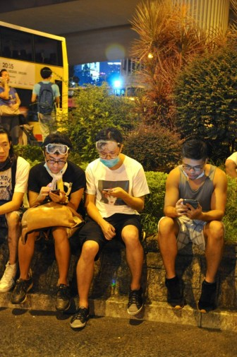 Among the crowd are those wearing goggles and masks. Post tear-gas, they sit on the roadside with their phones