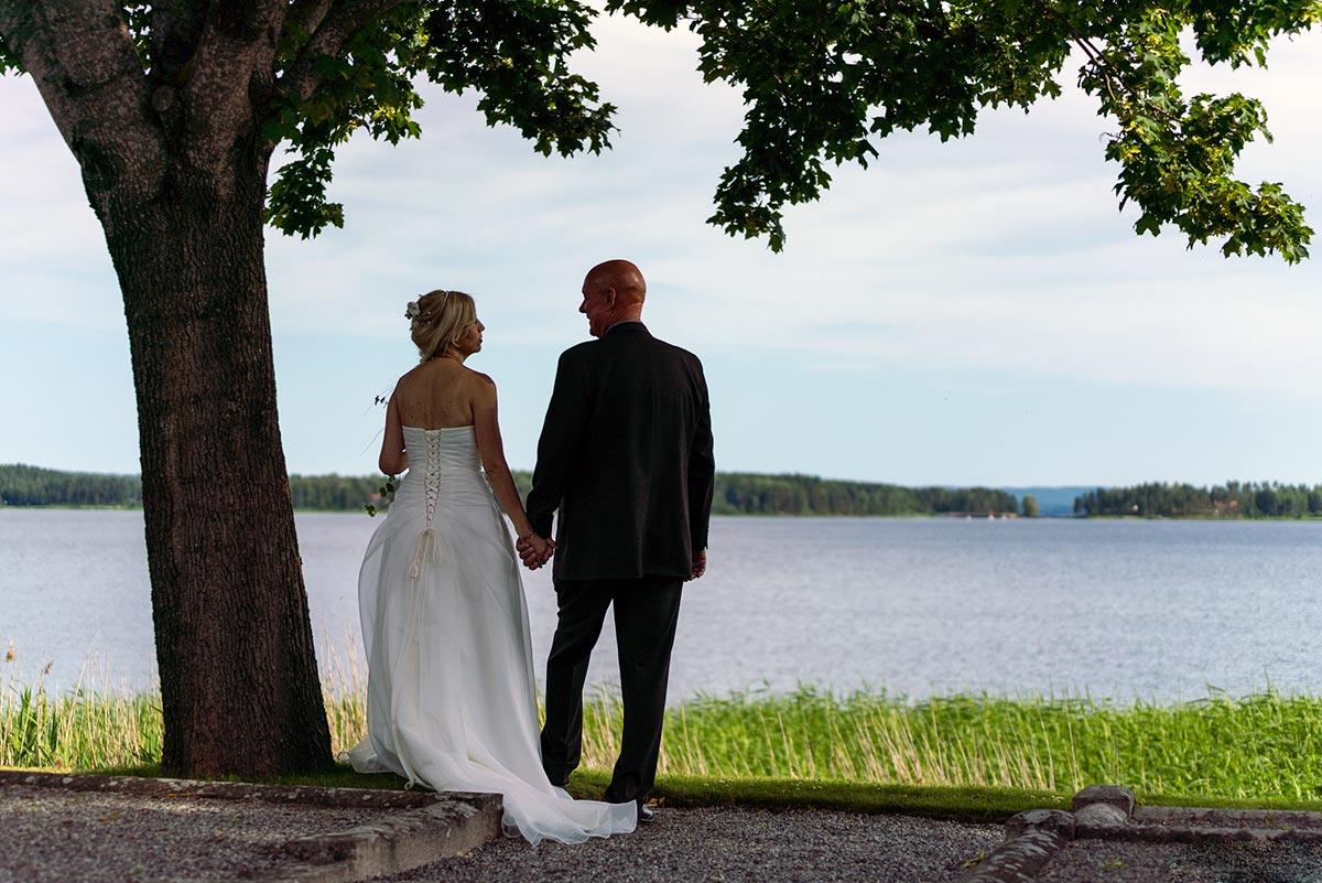 Bröllopspar håller varandras hand under ett träd vid Glafsfjorden Arvika
