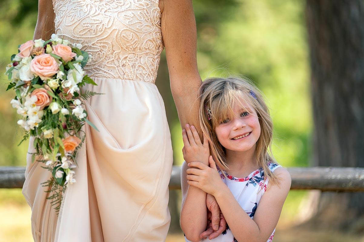 Liten flicka håller i brudens arm på bröllopsfest på Avelsbols hembygdsgård Arvika