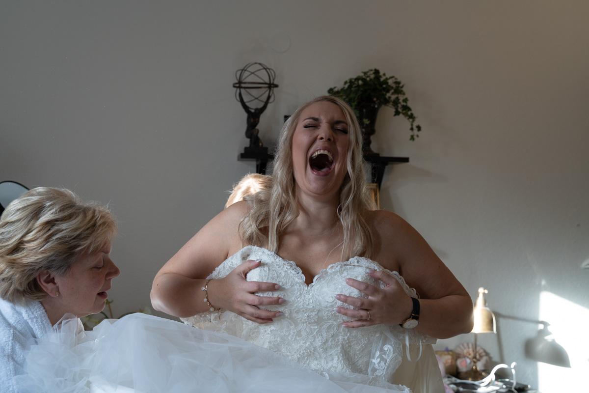 Bruden får hjälp med att klä sig och håller sig för brösten samtidigt som hon skrattar på Hotell Scandic Arvika