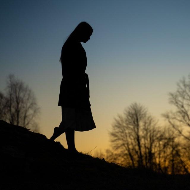 silhuet av kvinna som står på en kulle vid solnedgången