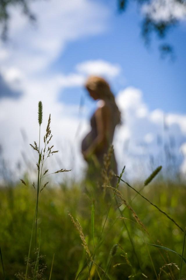 gravidbild av kvinna på sommaräng med fokus på detaljer i förgrunden