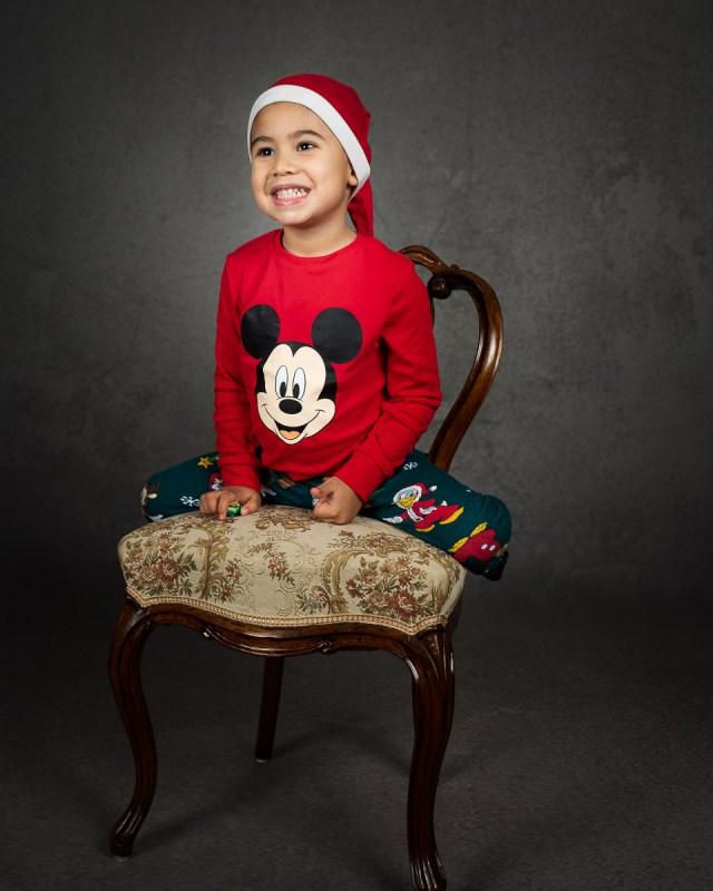 liten pojke utklädd i tomtekläder sitter på stol i studion