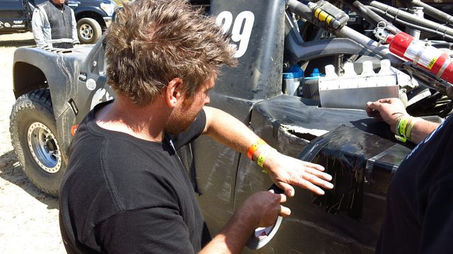 At our second fuel stop, Kory Halopoff repairs the #29's rear Fiberglas fender. Kory will drive the #250 for a leg of the race to give John a break.