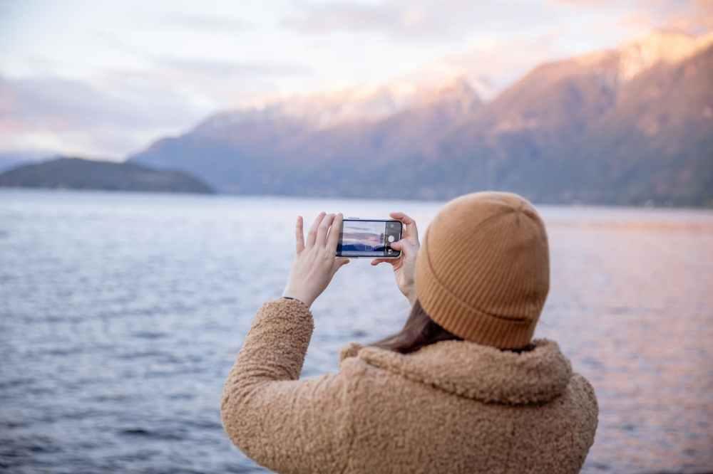 anonymous female traveler taking photo on smartphone while standing on coast and enjoying seascape