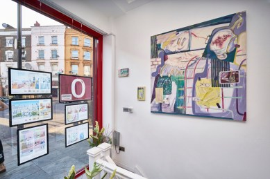 In the exhibition (especially in the window display), works are juxtaposed with real-life adverts of the agency - richly coloured interiors with generic interiors of property-as-tradable-asset.