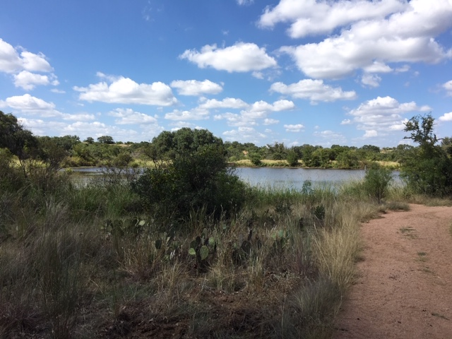 A small pond behind Enchanted Rock near a camping area.