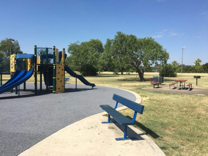 Benches and tables can be seen near the playground.
