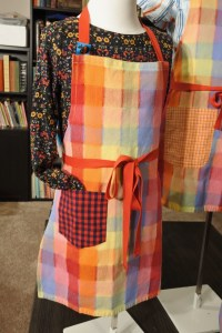 An Apron with blue and red gingham pocket, there is a sleeve sticking into the pocket.