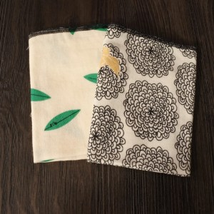 Image of two folded fabrics one with green leaves the other with black flowers and gold bird