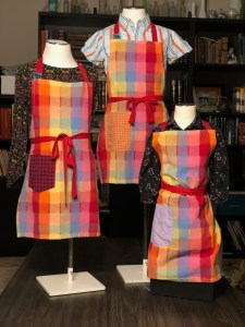 Three mannequins with rainbow plaid aprons.
