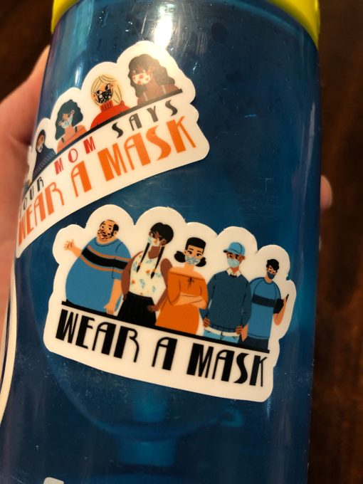 "Close up of a waterbottle with stickers that say ""wear a mask"""