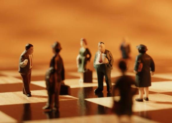 Small business people on chess board
