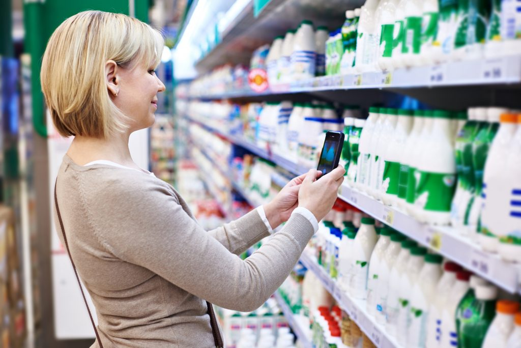 Woman photographing with smartphone label of dairy products