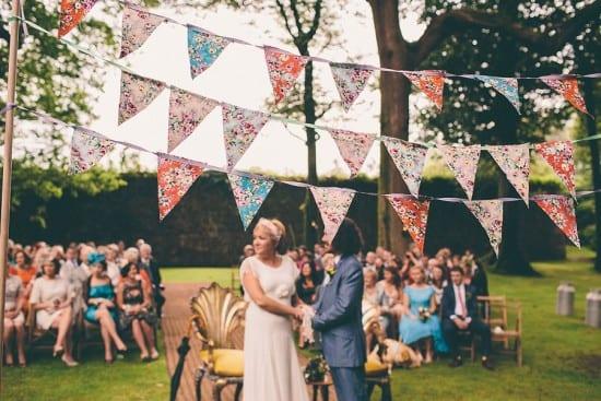 Casamento ao ar livre: altar decorado com cortina de bandeirinhas. Foto: Rubistyle.