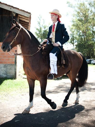Noivo gaúcho em trajes típicos chega a cavalo em casamento na fazenda. Foto: Beth Esquinatti.