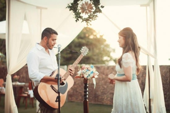 Noivo tocando violão em casamento diurno na praia ao ar livre.