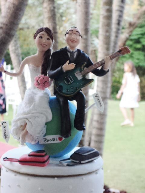 Noivinhos de topo de bolo: guitarra, música, viagem, malas, globo terrestre.