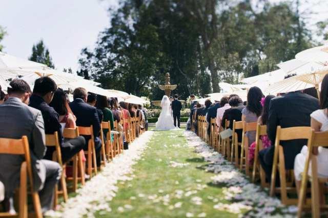 Convidada com sombrinha oriental em casamento no campo. Foto: Boutwell Studio.